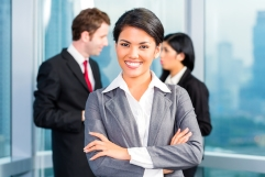Asian business team in office, woman in front with skyline