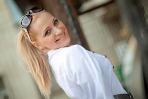 Uśmiechnięta blondynka w białej koszuli