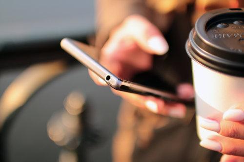 Kobieta trzyma telefon komórkowy i kubek z kawą