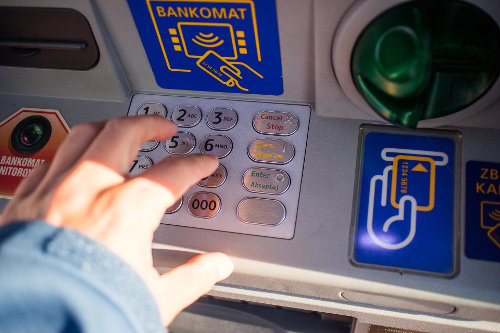 Mężczyzna wystukuje pin w bankomacie